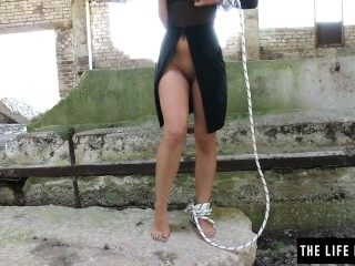 Sexy milf fucking herself hard in a collapsed building while tied with rope